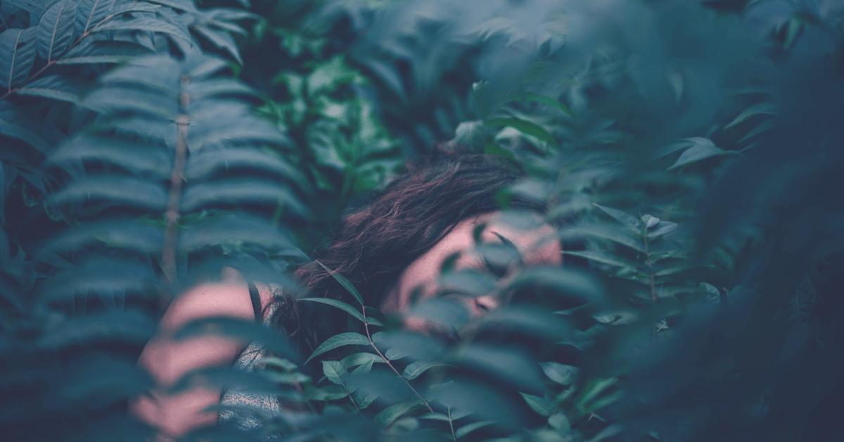 Lucid Dreaming woman sleeping in jungle leaves
