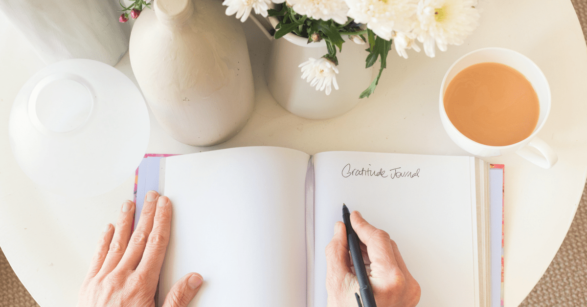 Hands pen writing in gratitude journal with coffee and flowers